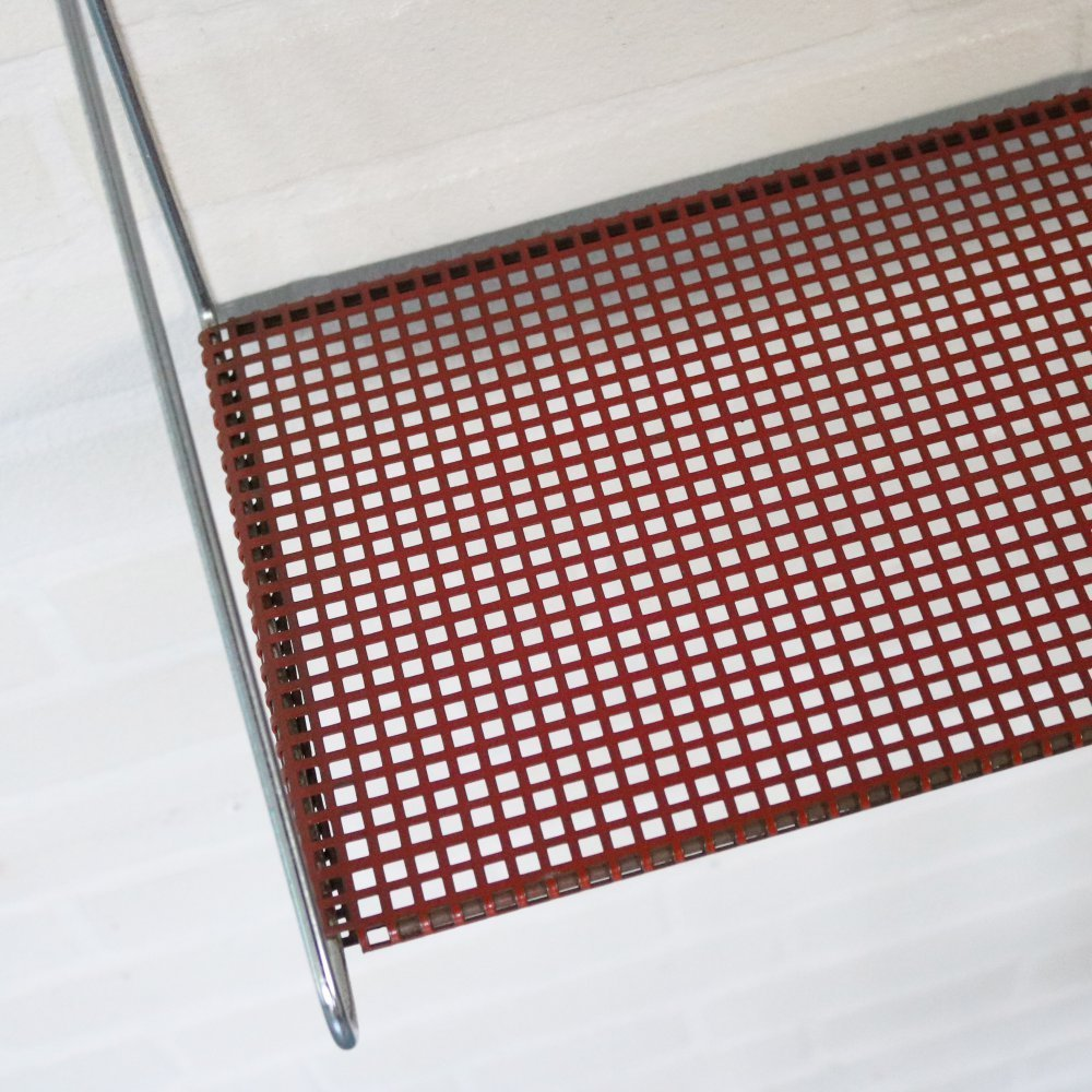 Wall mount book shelf in red perforated metal by Pilastro Holland
